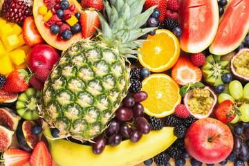 Wall Mural - Delicious fruit background mango pomegranate raspberries papaya oranges pineapple berries, selective focus, top view
