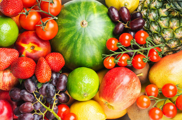 Wall Mural - Healthy raw rainbow fruits, mango papaya strawberries limes watermelon pineapple tomatoes background, top view, selective focus