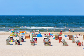 Unrecognisable people relax on a Baltic sea beach on Usedom island in Swinoujscie city, Poland