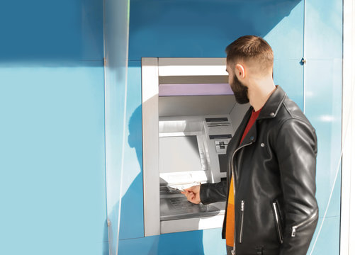 Young man taking money from cash machine outdoors