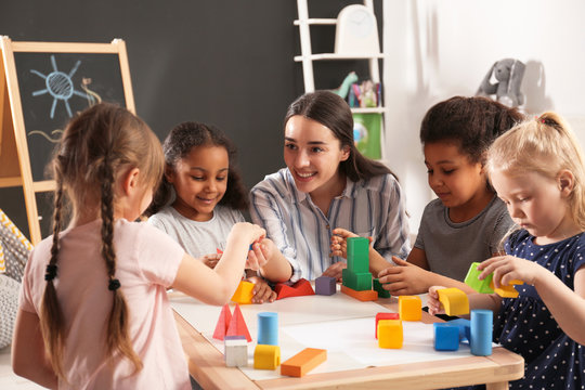 Cute little children and nursery teacher playing with building blocks in kindergarten. Indoor activity