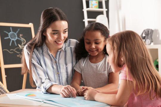 Cute little children with nursery teacher reading book at table in kindergarten. Indoor activity