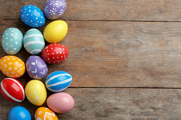 Flat lay composition of painted Easter eggs on wooden table, space for text
