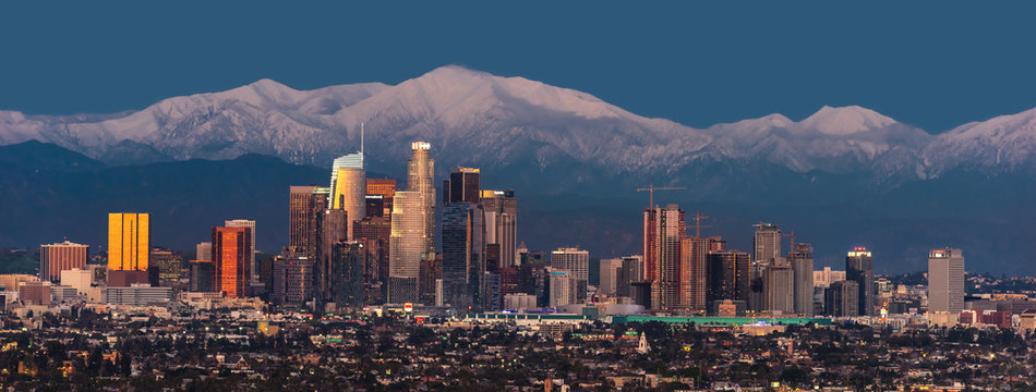 Downtown Los Angeles skyline with snow capped mountains behind at twilight
