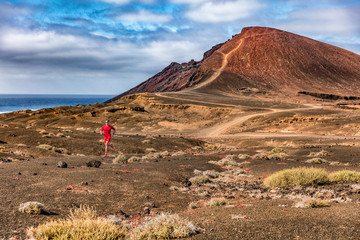 Athlete runner man trail running on volcanic mountain background terrain. Sports and fitness. Hero shot on nature landscape.