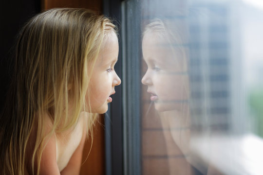 Beautiful little girl with blonde hair looking into a window at home