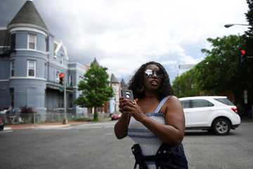 A woman stops on the road to take a picture of a car parking collision in Washington