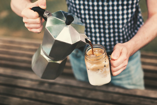 A man pouring ice coffee from a coffee maker to a glass jar with milk.