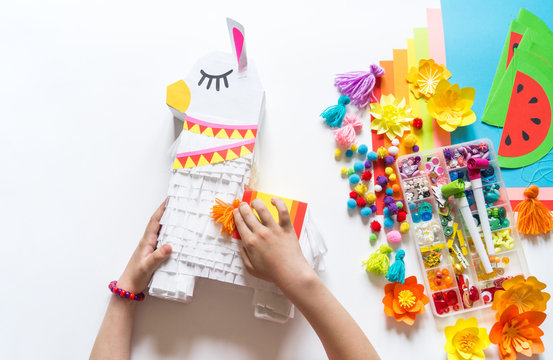 Diy cinco de mayo Mexican Pinata llama made cardboard and crepe paper your own hands on a white background.