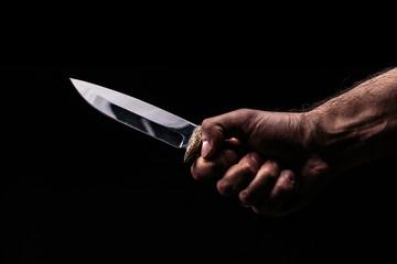 Hunting knife in hand on dark background - fototapety na wymiar