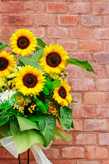 Fototapete - Bouquet of beautiful sunflowers on brick background