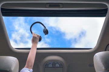 girl holds her hand with handphones out from open hatch of a vehicle. Travel lifestyle concept