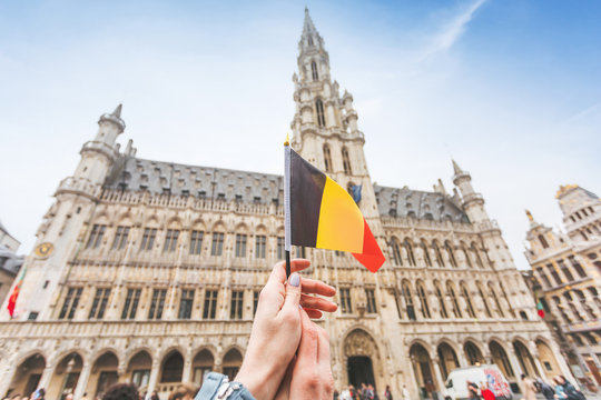 Woman tourist holds in her hand a flag of Belgium against the background of the Grand-Place Square in Brussels, Belgium