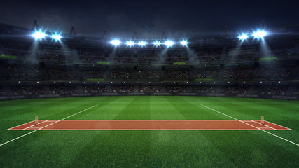 Illuminated round cricket stadium full of fans at night upper side view