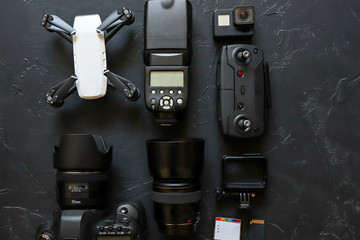 A set of photographer and videographer on a black background. Digital camera, memory card, action camera, drone, remote control, telephone and camera. Top view on black background table.