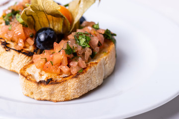 Delicious Italian antipasti bruschetta on white background. Macro. Copy space.