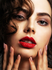 Face of a beautiful woman with a smoky eye makeup and red lipstick