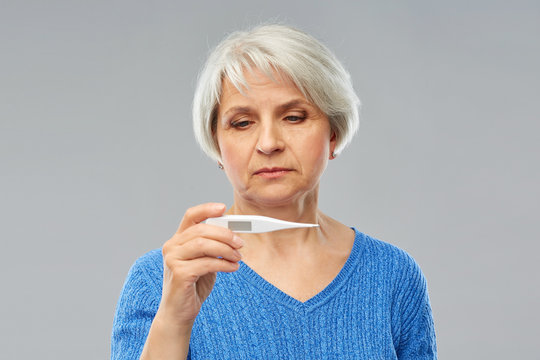 health and fever concept - sick senior woman with thermometer over grey background