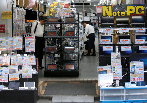 Men look at a display of computers at a store in Tokyo