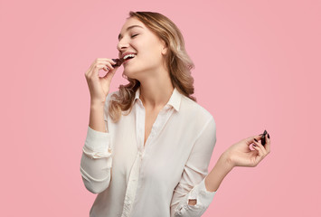 Young woman eating chocolate with closed eyes