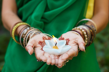 Beautiful woman in traditional Muslim Indian wedding green sari dress hands with henna tattoo mehndi pattern jewelry and bracelets hold burning lotus candle Summer culture festival celebration concept Fototapete