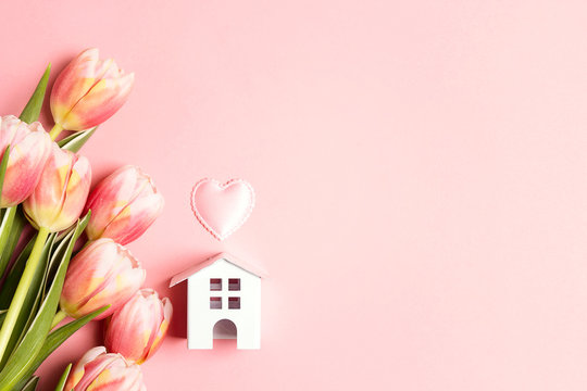 Miniature white toy house with tulip flowers on pink  background.