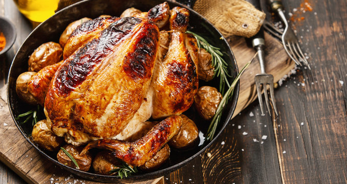Baked whole chicken with spices on pan