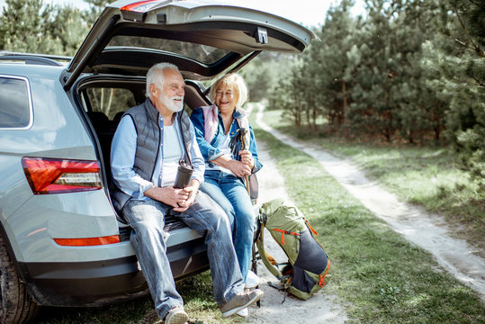 Senior couple sitting at the car trunk, enjoying nature while traveling in the young pine forest
