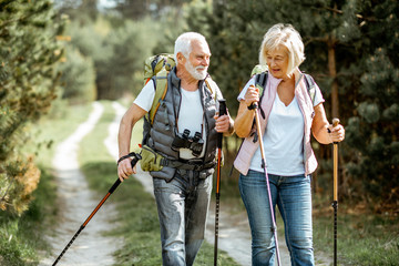 Happy senior couple hiking with trekking sticks and backpacks at the young pine forest. Enjoying nature, having a good time on their retirement Wall mural