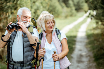 Portrait of a happy senior couple standing together with binoculars, backpacks and trekking sticks while hiking in the forest. Concept of an active lifestyle on retirement