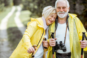 Portrait of a happy senior couple in yellow raincoats hiking with trekking sticks in the young pine forest. Concept of an active lifestyle on retirement