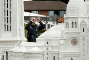 A tourist takes a picture with his phone at the Mini Europe park in Brussels