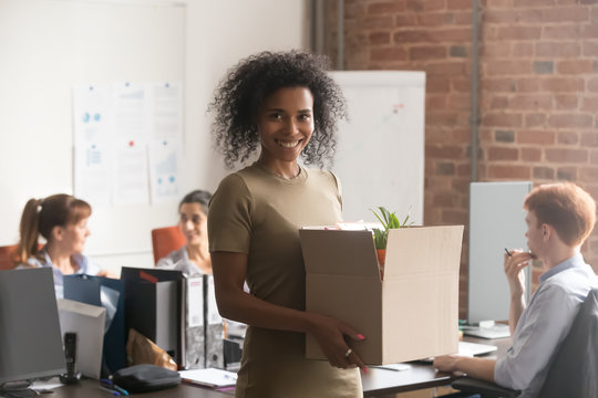 Excited black female newcomer holding box with personal belongings