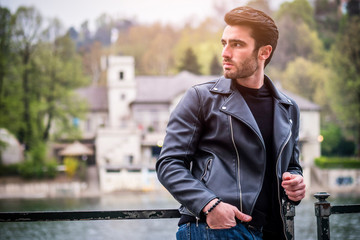 One handsome young man in urban setting in modern city, standing, wearing black leather jacket and jeans, looking away Wall mural