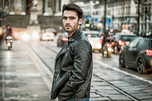 b38e3b1a One handsome young man in urban setting in modern city, standing, wearing  black leather jacket and jeans, looking at camera