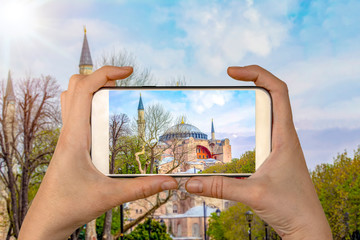Tourist taking a picture in front of  The  Hagia Sophia Museumat spring, Istanbul, Turkey. Travel concept