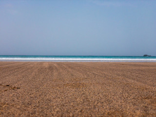 Sand grains of a beach in the foreground and sea with waves in the background