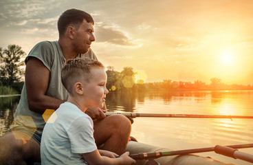Happy Father and Son together fishing from a boat at sunset time Wall mural