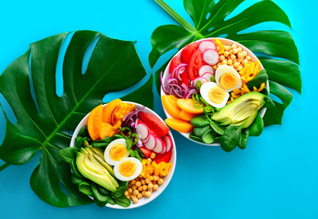 Buddha bowl with boiled eggs served on monstera leaves