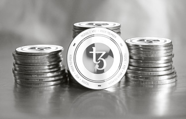 Tezos (XTZ) digital crypto currency. Stack of silver coins. Cyber money.