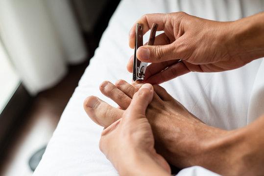 young caucasian man cutting his toenails