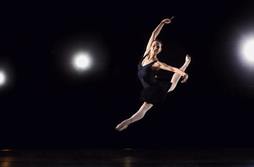 Ballerina in a black suit is jumping on a black background.