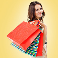 Happy woman with shopping bags, over yellow