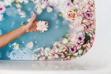 Top view of bath filled with blue bubble water and petals with woman's hand holding flower, spa or...