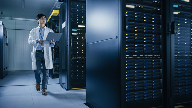 In Data Center: Male IT Technician Wearing White Coat Walking alongside Server Racks, Uses Laptop Computer to Run Maintenance Diagnostics Tools. He is Wearing Lab Coat and Working with Data.