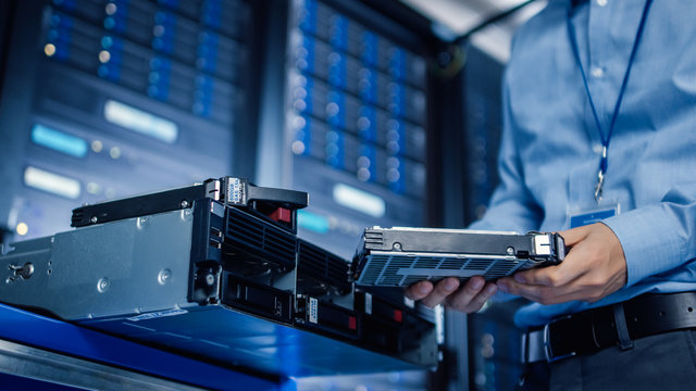 In the Modern Data Center: IT Engineer is Holding New HDD Hard Drive Prepared for Installing Hardware Equipment into Server Rack. IT Specialist Doing Maintenance and Updating Hardware.