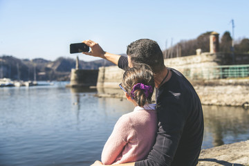 Tuinposter Young father with daughter sitting on the lake shore watching the boats at sea Daddy make selfie with little girl. Relaxing peaceful weekend Concept of family and affection, strong bond