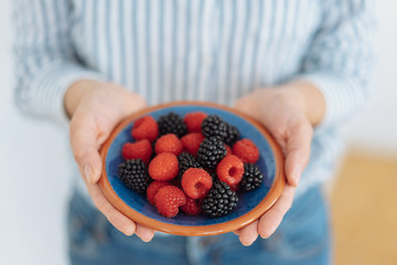 Woman holding a plate of fresh mixed berries