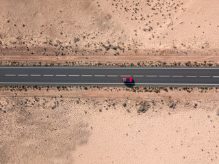 Aerial view of a red car in the desert valleys of the island of Lanzarote, Canary Islands, Spain. Paths and roads