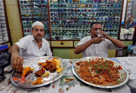 Muslims eat Iftar meals inside a shop selling eyeglasses during the holy fasting month of Ramadan in Kolkata